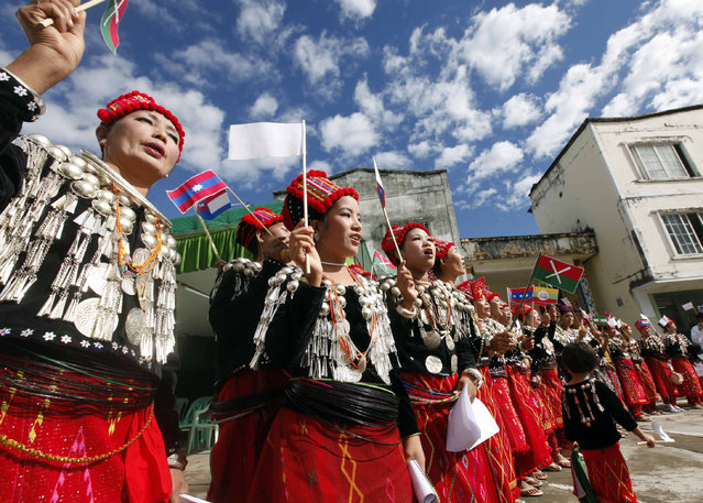 Clad in Kachin traditional costumes, women dance with miniature flags of ethnic rebels as they welcome other ethnic rebels during a nationwide ceasefire conference at the headquarters of KIA in Laiza, a border town of China and Myanmar, Kachin State, Myanmar, Tuesday, October 29, 2013. From 1961 until 1994, the KIA fought a grueling and inconclusive war against the Burmese junta for independence, but now the groups goal is for autonomy within a federal union. The Kachins are a coalition of six tribes whose homeland encompasses territory in Yunnan, China and Northeast India, in addition to Kachin State in Burma. (Photo by Khin Maung Win/AP Photo)
