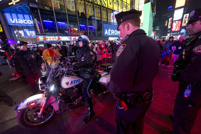 A New York City motorcycle officer makes his way through Times Square during New Year's Eve celebrations in New York December 31, 2014. (Photo by Keith Bedford/Reuters)