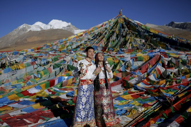 Jing Li (L) and her husband Ke Xu wear Tibetan traditional costumes as they pose for their wedding photos in front of Tibetan prayer flags at the Nianqing Tanggula mountain pass in the Tibet Autonomous Region, China November 18, 2015. (Photo by Damir Sagolj/Reuters)