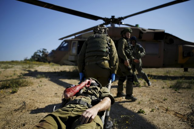Israeli soldiers evacuate their comrade playing the role of a wounded person during an exercise, near Kibbutz Zikim, close to the border with northern Gaza November 20, 2015. An announcement from Israeli Defence Forces spokesperson's unit said the drill simulated the evacuation of wounded people from a mass-casualty incident in an open area. (Photo by Amir Cohen/Reuters)