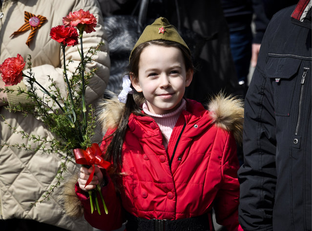 A girl carries flowers as people hold portraits of their relatives who fought in World War II during an Immortal Regiment march on the day of the 73 rdanniversary of the victory over Nazi Germany in the Great Patriotic War of 1941-1945, the Eastern Front of the Second World War in Vladivostok, Russia on May 9, 2018. (Photo by Yuri Smityuk/TASS)