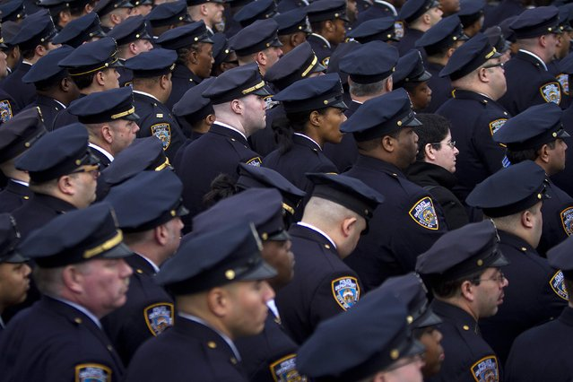 Police officers from the 84th Precinct listen during the funeral for slain New York Police Department officer Wenjian Liu in the Brooklyn borough of New York January 4, 2015. (Photo by Carlo Allegri/Reuters)