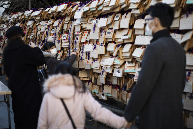 """A girl with her family members hangs her """"ema"""" board with her wish written on it in Yushima Tenmangu shrine in Tokyo on New Year's Day, Friday, January 1, 2021. (Photo by Hiro Komae/AP Photo)"""