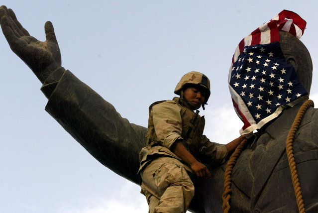A U.S. Marine covers the face of a statue of Iraqi President Saddam Hussein with a U.S. flag in Baghdad, Iraq April 9, 2003. (Photo by Goran Tomasevic/Reuters)