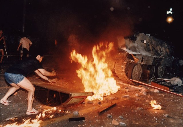 A student protester puts barricades in the path of an already burning armored personnel carrier that rammed through student lines during an army attack on anti-government demonstrators in Beijing's Tiananmen Square, early June 4, 1989. A govenment soldier who escaped the armored vehicle was killed by demonstrators. Pro-democracy protesters occupied the square for seven weeks; hundreds died in the early hours of June 4, 1989 when troops shot their way through Beijing's streets to retake the square. (Photo by Jeff Widener/AP Photo)