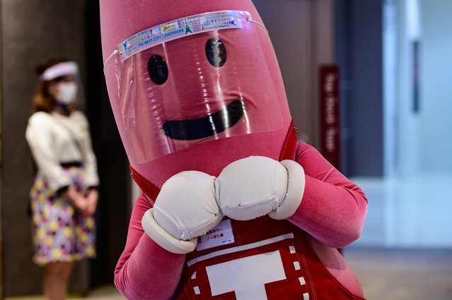 A person dressed as the mascot of Tokyo Tower wears a face shield while waiting to greet patrons at the entrance of the 332.9m (1,092ft.) high tower on May 28, 2020, as the city's landmark reopened following the lifting on May 25 of the state of emergency, imposed due to the COVID-19 novel coronavirus outbreak. (Photo by Philip Fong/AFP Photo)