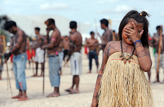 Munduruku natives rally in front of  the Planalto Palace in Brasilia, on June 6, 2013. Five indigenous tribes are calling for legislation under which they would have to be consulted prior to any official decision affecting them with respect to the dam's construction. Belo Monte, which is being built at a cost of $13 billion, is expected to flood an area of 500 square km along the Xingu River, displacing 16,000 people, according to the government. Some NGOs have estimated that some 40,000 people would be displaced by the massive project. Indigenous groups say the dam will harm their way of life while environmentalists warn of deforestation, greenhouse gas emissions and irreparable damage to the ecosystem. (Photo by Evaristo Saevaristo/AFP Photo)