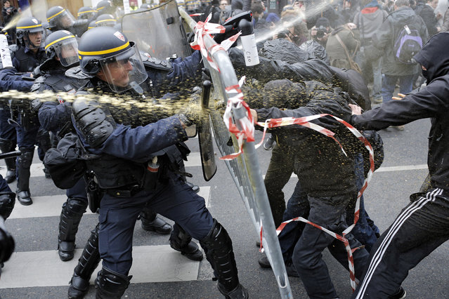 Policemen fight with activists during a protest ahead of the 2015 Paris Climate Conference at the place de la Republique, in Paris, Sunday, November 29, 2015. (Photo by Laurent Cipriani/AP Photo)