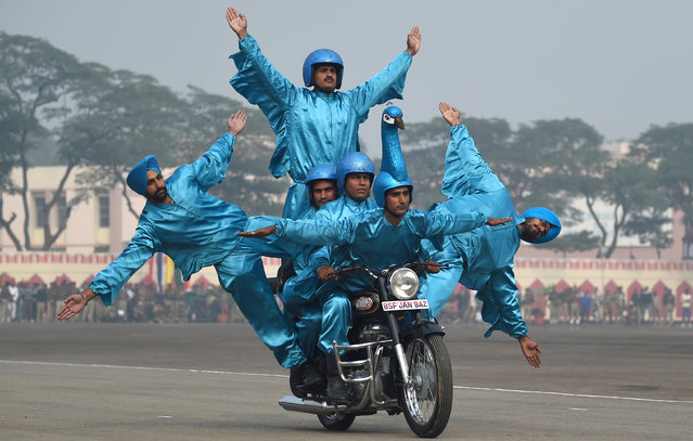 Members of the Indian Border Security Force (BSF) demonstrate their skills on motor-bikes during the BSF Golden Jubilee Day celebration in New Delhi on December 1, 2015. (Photo by Money Sharma/AFP Photo)