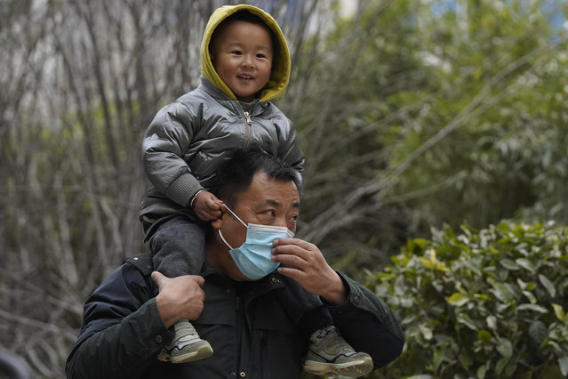 A child holds on to the ears of a masked man as she sits on his shoulders on a street of Wuhan in central China's Hubei province, Saturday, January 16, 2021. (Photo by Ng Han Guan/AP Photo)