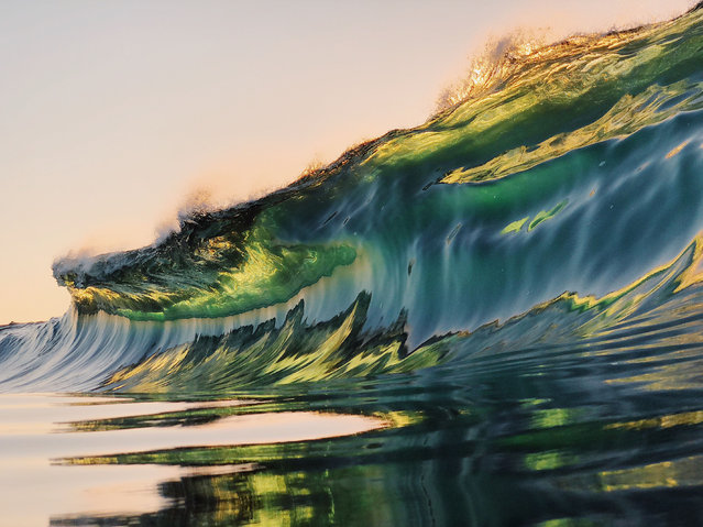 """""""I am obsessed with photographing waves when there is interesting light, such as on sunrise or sunset – I love the light that leaks through the waves"""". (Photo by Ryan Pernoski/Caters News Agency)"""