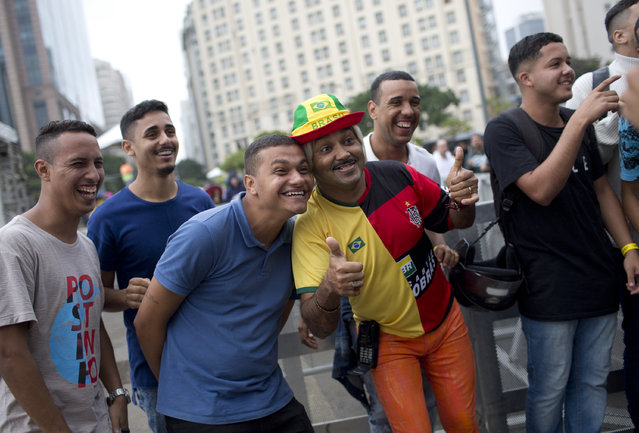 Fans pose for a photo as they watch the group A, 2018 soccer World Cup opening match between Russia and Saudi Arabia on a outdoors television screen, at Praca Maua, in Rio de Janeiro, Brazil, Thursday, June 14, 2018. (Photo by Silvia Izquierdo/AP Photo)