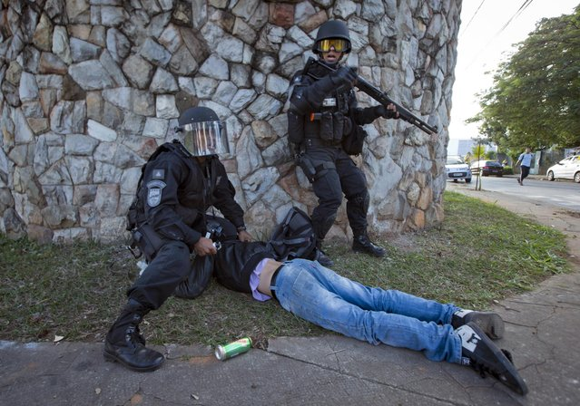 Riot police detain a man during a demonstration in Belo Horizonte, Brazil, Wednesday, June 26, 2013.  Brazilian anti-government protesters in part angered by the billions spent in World Cup preparations and police clashed Wednesday near the stadium hosting a Confederations Cup football match, with tens of thousands of demonstrators trying to march on the site confronting police firing tear gas and rubber bullets. (Photo by Victor R. Caivano/AP Photo)