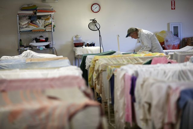 A worker checks on birds being dried after a cleaning at the International Bird Rescue in Fairfield, California January 20, 2015. (Photo by Robert Galbraith/Reuters)