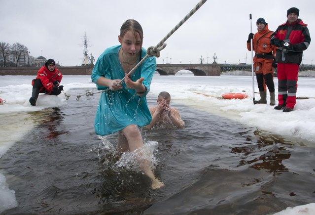 Rescue workers control Russian Orthodox believers swimming in the icy water on Epiphany in the Neva River in St.Petersburg, Russia, Monday, January 19, 2015. (Photo by Dmitry Lovetsky/AP Photo)