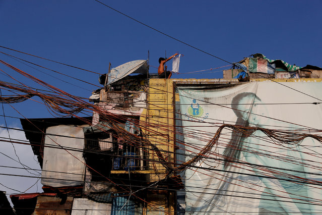 Electric wires are seen as a boy plays on the rooftop of Vitas Tenement, a government housing building, in Tondo, Manila, Philippines, May 8, 2018. (Photo by Erik De Castro/Reuters)