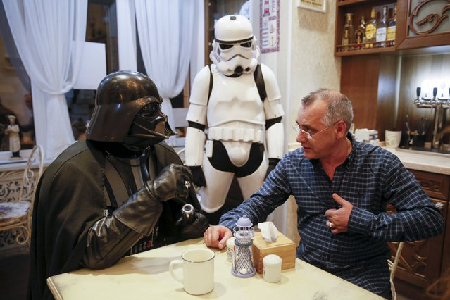 Darth Mykolaiovych Vader (L), who is dressed as the Star Wars character Darth Vader, poses for a picture as he speaks with a supporter in a cafe in Odessa, Ukraine, December 3, 2015. Darth Vader was bent on galactic domination, but his Ukrainian namesake enjoys more mundane pursuits: local politics, walking the family dog and a spot of embroidery. (Photo by Valentyn Ogirenko/Reuters)