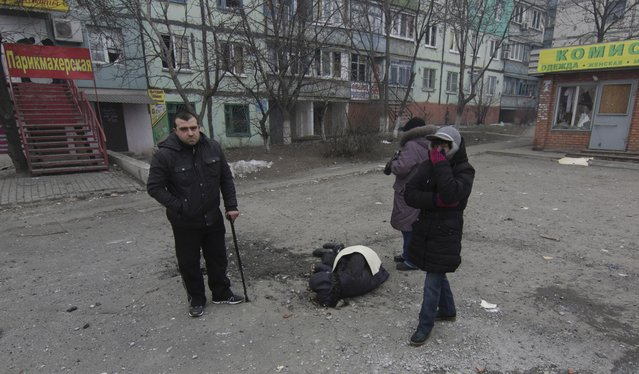 A dead body surrounded by local residents lays on the ground in a residential area in Mariupol, Ukraine, Saturday, January 24, 2015. (Photo by Sergey Vaganov/AP Photo)