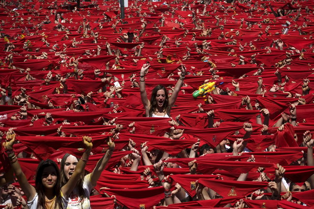 """Participants hold red scarves as they celebrate the """"Chupinazo"""" marking the start at noon sharp of the San Fermin Festival at Castle square in Pamplona, northern Spain on July 6, 2013. Ten of thousands of people packed Pamplona's streets for a drunken kick-off to Spain's best-known fiesta: the nine-day San Fermin bull-running festival. (Photo by Pedro Armestre/AFP Photo)"""