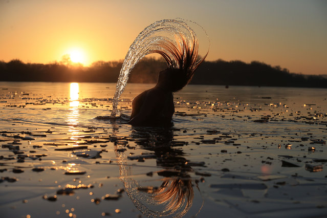 An open water swimmer surfaces as she enjoys a socially-distanced dawn swim after breaking the ice on the surface of a lake near Scunthorpe, northern England, January 9, 2021. Faced by a sharp rise in coronavirus infections, driven by the new strain, England entered a strict lockdown on January 5, 2021, with schools and non-essential shops closed for at least six weeks after previous measures failed to halt the steep rise in cases. (Photo by Lindsey Parnaby/AFP Photo)