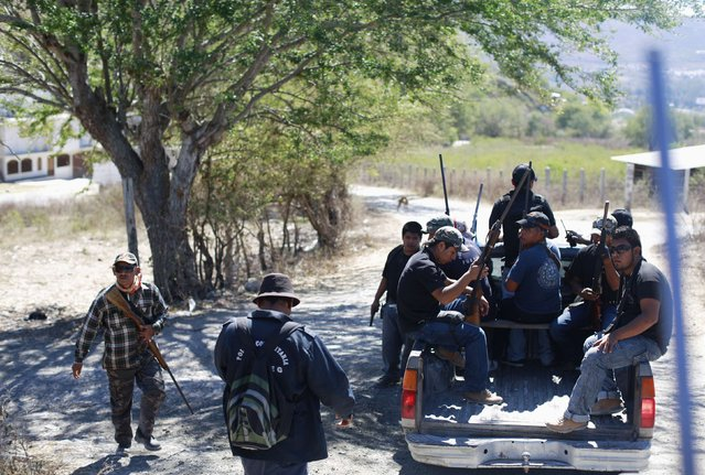 Members of the Community Police of the FUSDEG (United Front for the Security and Development of the State of Guerrero) patrol in a truck in the village of Petaquillas, on the outskirts of Chilpancingo, in the Mexican state of Guerrero, February 1, 2015. (Photo by Jorge Dan Lopez/Reuters)