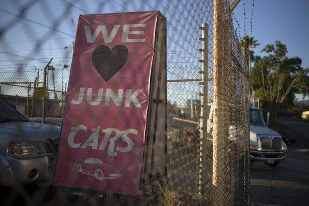 In this Wednesday, November 11, 2015 photo, a sign is seen near the entrance to Aadlen Brothers Auto Wrecking, also known as U Pick Parts, in the Sun Valley section of Los Angeles. It's not just a junkyard or even a really big junkyard, but a living, breathing monument to Los Angeles pop culture. But the family business is closing on New Year's Eve, and everything must go by then, the cars, the shark, the arches, even the giant car-crushing machine. (Photo by Jae C. Hong/AP Photo)
