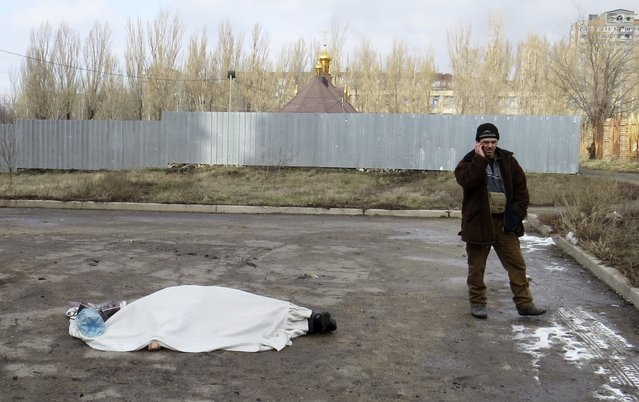 A man speaks on the phone next to the body of a victim, near a hospital in Donetsk February 4, 2015. A shell hit a hospital in the east Ukrainian rebel-controlled city of Donetsk on Wednesday, killing or injuring several people, the city administration said. (Photo by Maxim Sergeev/Reuters)