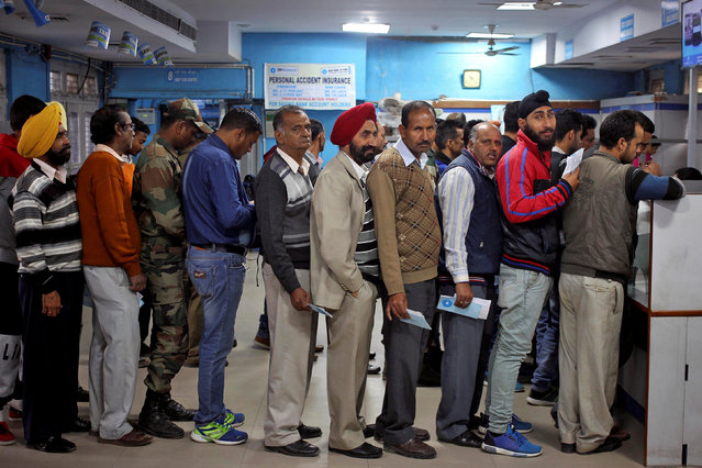 People queue as they wait for their turn to exchange or deposit their old high denomination banknotes in Jammu, November 24, 2016. (Photo by Mukesh Gupta/Reuters)