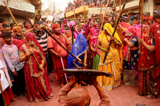 Indian women from Barsana village beat a villager from Nandgoan with wooden sticks as he teases them during Lathmar holi festival celebrations at the legendary hometown of Radha, consort of Hindu god Krishna, in Barsana, India, Tuesday, March 23, 2021. During Lathmar Holi the women of Barsana beat men from Nandgaon, the hometown of Krishna, with wooden sticks in response to their teasing as they depart the town. (Photo by AP Photo/Stringer)