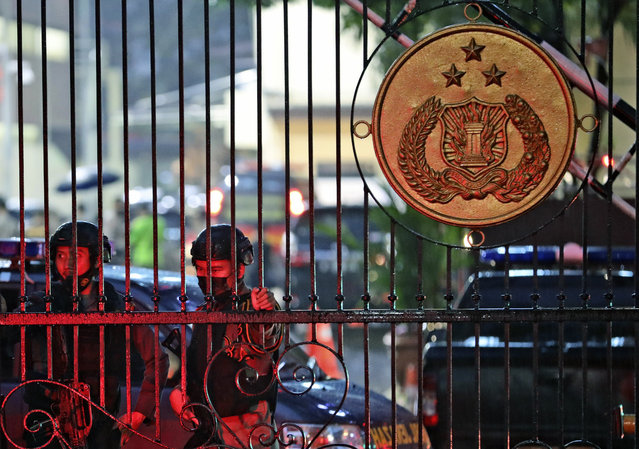 Police officers stand guard at the main gate of the National Police Headquarters following a suspected militant attack in Jakarta, Indonesia, Wednesday, March 31, 2021. A woman entered the Indonesian National Police Headquarters in Jakarta and pointed a gun at several officers before being shot dead by police, in the latest in a series of suspected militant attacks in the world's most populous Muslim nation. (Photo by Dita Alangkara/AP Photo)