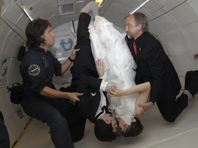 Bride Erin Finnegan and bridegroom Noah Fulmor, both of New York, are helped by Zero Gravity Corporation co-founder Richard Garriott (R), and Bryan Rapoza as they seal their wedding with a kiss, while floating upside down, during the first weightless wedding aboard a specially-equipped Boeing 727, while flying over the Gulf of Mexico after taking off from Titusville, Florida, June 20, 2009. Finnegan and Fulmor floated into matrimony on Saturday thousands of feet (metres) above the Gulf of Mexico in what organizers said was the world's first weightless wedding held in zero gravity conditions. To recreate the weightless experience without going into space, the plane executed parabolic flight maneuvers, climbing sharply and descending several times during the one-hour flight. (Photo by Phelan Ebenhack/Reuters)