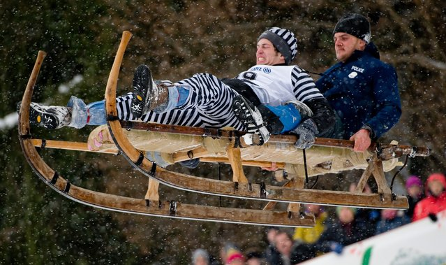Two men ride a horn sled over the track at the traditional horn sled race in Gaisslach, Germany, 08 February 2015. Over 100 sled riders, some of them costumed, participate in this traditional event, riding their sleds down the 1.5 kilometer-long track. (Photo by Sven Hoppe/EPA)
