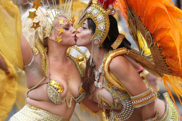 Performers in costume kiss as they take part in the carnival on the main Parade day of the Notting Hill Carnival in west London on August 27, 2018. Nearly one million people are expected by the organizers Sunday and Monday in the streets of west London' s Notting Hill to celebrate Caribbean culture at a carnival considered the largest street demonstration in Europe. (Photo by Daniel Leal-Olivas/AFP Photo)