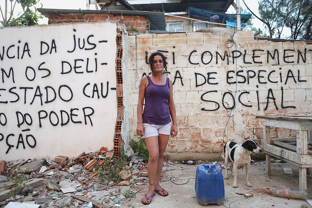 Longtime resident Sandra Maria de Sousa poses near her home in front of anti-demolition grafitti in the mostly demolished Vila Autodromo favela community, a former fishing colony, on January 6, 2016 in Rio de Janeiro, Brazil. Most residents of the favela community have moved out and had their properties demolished after receiving compensation for their homes which are located directly adjacent to the Olympic Park under construction for the Rio 2016 Olympic Games. (Photo by Mario Tama/Getty Images)