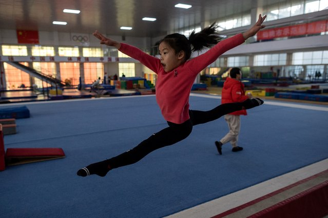 In this picture taken on January 11, 2021, young gymnast Du Xiyun trains at the Li Xiaoshuang Gymnastics School in Xiantao, Hubei province. (Photo by Nicolas Asfouri/AFP Photo)