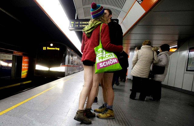 """A couple kisses while participating in the """"No Pants Subway Ride"""" in Vienna, Austria,on January 10, 2016. The No Pants Subway Ride is an annual event which was started in 2002 by Improv Everywhere in New York, the goal is for riders to get on the subway train dressed in normal winter clothes without pants and keep a straight face. (Photo by Georg Hochmuth/AFP Photo/APA)"""