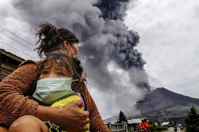 A mother holds her child as Mount Sinabung spews ash and hot lava during an eruption in Perteguhan village in Karo district, Indonesia's north Sumatra province, on September 17, 2013. (Photo by Roni Bintang/Reuters)