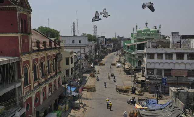 Birds fly over the deserted old city during a weekend lockdown to curb the spread of coronavirus in Prayagraj, India, Saturday, April 24, 2021. (Photo by Rajesh Kumar Singh/AP Photo)
