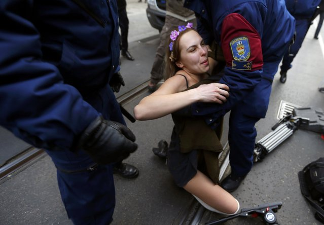 Police detain an activist of Ukrainian womens' rights group FEMEN during a protest against a visit of Russian President Vladimir Putin in Budapest February 17, 2015. (Photo by Laszlo Balogh/Reuters)