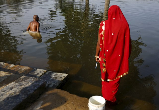 Visually-impaired Kartik Ram Sadhu, 67, a follower of Ramnami Samaj, who has tattooed the name of the Hindu god Ram on his body, bathes in a pond in the village of Arjuni, in the eastern state of Chhattisgarh, India, November 15, 2015. (Photo by Adnan Abidi/Reuters)