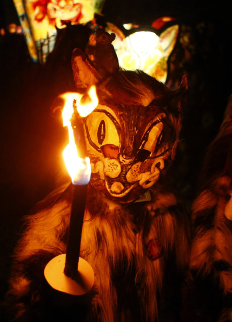 A carnival reveller carries a burning stick during the traditional Swiss Chienbaese celebration in Liestal near Basel February 22, 2015. (Photo by Ruben Sprich/Reuters)
