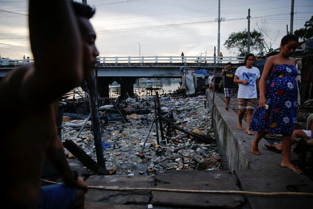 People pass under C-3 bridge in North Bay Boulevard South (NBBS), a Navotas City district of slums and waterways with a high number of drug war deaths, in Manila, Philippines November 3, 2016. (Photo by Damir Sagolj/Reuters)