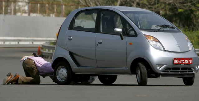 A journalist inspects a 'Nano' car during a test drive session at the company's plant in Pimpri, south-east of Mumbai in this March 25, 2009 file photo. (Photo by Punit Paranjpe/Reuters)