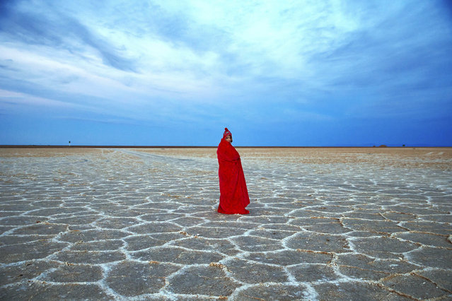 In this picture taken on Thursday, December 1, 2016, an Iranian woman covers herself with a blanket due to the cold,  while visiting Khour salt lake during her tour of the Mesr desert about 305 miles (500 kilometers) southeast of the capital Tehran, Iran. Deserts make up parts of Iran which have recently become tourist destination for young Iranians looking for a break on their weekend. The increase in tourists to the desert has stimulated economic growth in the area. (Photo by Ebrahim Noroozi/AP Photo)