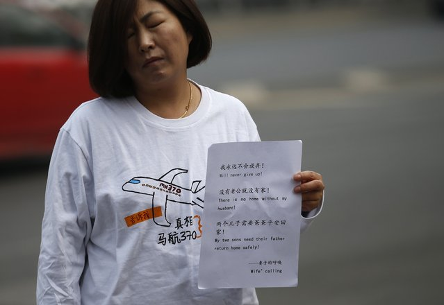 Cheng Liping, whose husband Ju was onboard the missing Malaysia Airlines flight MH370, holds a sign during an interview with Reuters in Beijing March 8, 2015. Malaysian and Chinese officials say they are committed to the search for MH370 and in assisting families who are still waiting for concrete information on what happened to their loved ones a year ago.