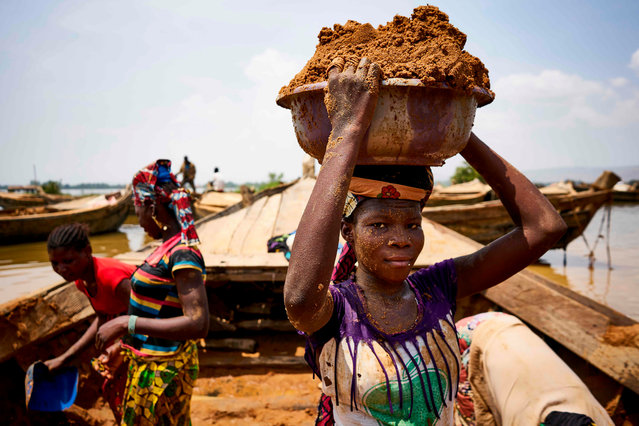 Malian women unload river sand from boats moored in the port of Bamako on October 1, 2018. (Photo by Michele Cattani/AFP Photo)