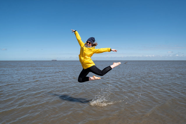 Tizia jumps at the beach following the ease of pandemic lockdown measures on May 23, 2021 in Cuxhaven-Duhnen, Germany. Authorities are easing lockdown measures across Germany, enabling restaurants to offer outdoor service, hotels to accommodate tourists, cultural institutions to perform and other activities to resume. Covid infection rates have been falling consistently and the national average is now below 75 per 100,000 over a seven-day period. Meanwhile the pace of vaccinations is climbing, with approximately 40% of the population having received a first dose. (Photo by David Hecker/Getty Images)