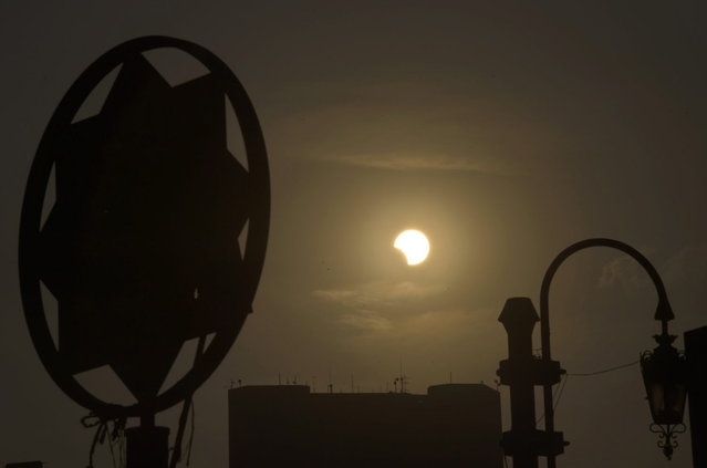 A partial solar eclipse is seen over the Egyptian capital Cairo, on November 3, 2013. The rare solar eclipse will sweep across parts of Africa, Europe and the United States as the moon blocks the sun either fully or partially, depending on the location. (Photo by Khaled Desouki/AFP Photo)