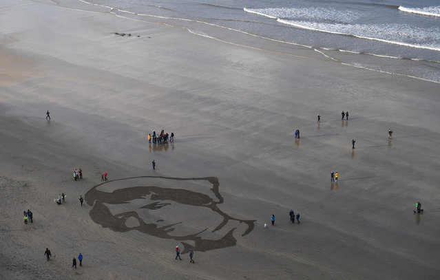 People gather to look at an Armistice day sand portrait of Imperial Military Nurse Rachel Ferguson who died in June 1918 during World War One, created as part of Danny Boyle's Pages of The Sea celebrations, on Downhill Beach in Coleraine, Northern Ireland, November 11, 2018. (Photo by Clodagh Kilcoyne/Reuters)