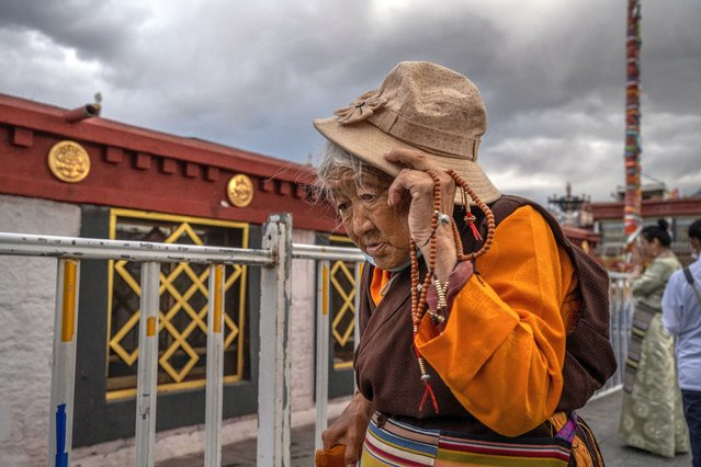 A Tibetan Buddhist woman walks the kora in front of the Jokhang Temple, a UNESCO heritage site, on June 1, 2021 in Lhasa, Tibet Autonomous Region, China. (Photo by Kevin Frayer/Getty Images)
